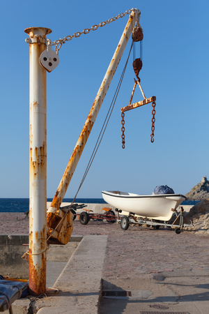 White fishing boat and small crane in port of Petrovac town, Montenegro photo