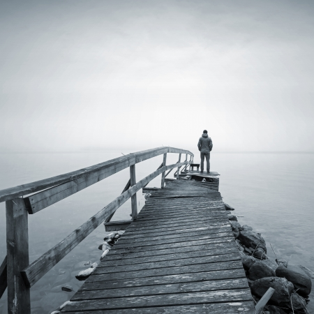 docks: A man on the old broken wooden pier starring at the foggy Sea Stock Photo