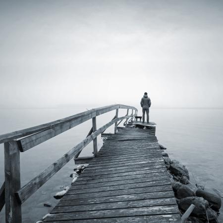 Een mens op de oude gebroken houten pier in de hoofdrol op de mistige zee