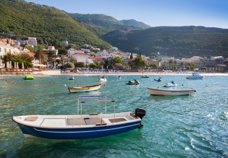 Fishing and pleasure boats float moored in Adriatic sea water. Petrovac town, Montenegro photo
