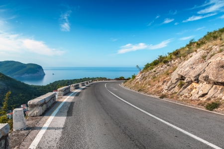mountain road: Turning mountain highway with blue sky and sea on a background