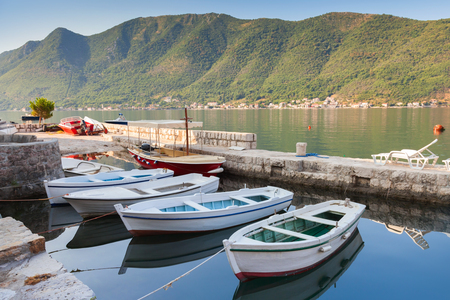 White fishing boats float moored in Perast town. Bay of Kotor, Montenegro photo