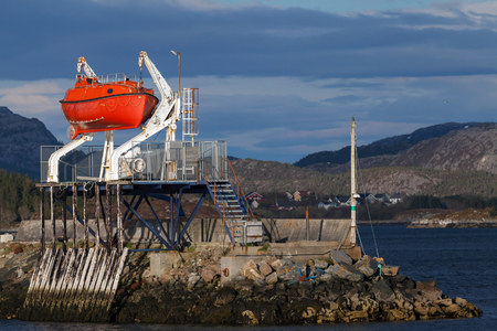 Red rescue boat on the coast in Norwegian town photo