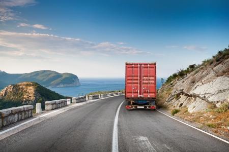 青い空と海を背景に山の道路で貨物トラック