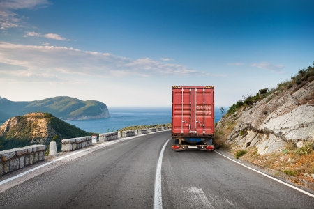 truck on highway: Cargo truck on the mountain highway with blue sky and sea on a background