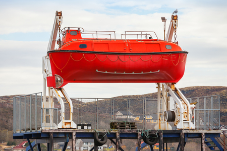 Red rescue boat stands on the coast in Norway photo