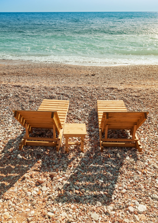 Two wooden sun loungers stand on the Adriatic Sea coast photo