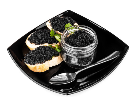 Sandwiches with black caviar and spoon on dark plate photo