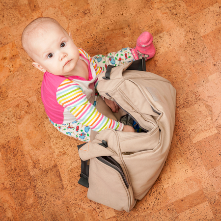 brown  eyed: Little brown eyed Caucasian baby delves into the bag