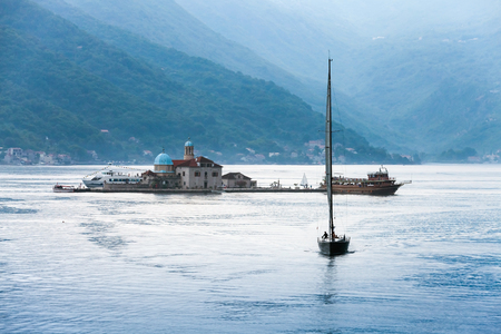 Bay of Kotor. Small island Our Lady of the Rocks and sailing yacht photo