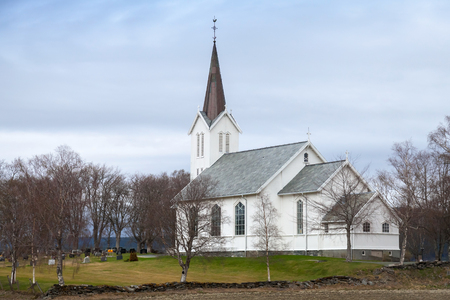 Traditional white wooden Norwegian Lutheran Church in small village photo