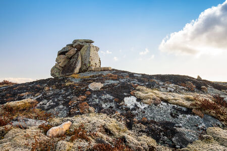 bessegen: Stone cairn as a navigation mark on the top of Norwegian rock Stock Photo