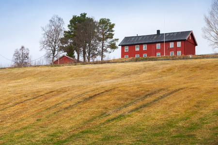 sprung: Sprung rural Norwegian landscape with red house and field Editorial