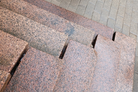 Old stairs made of red granite on gray pavement photo