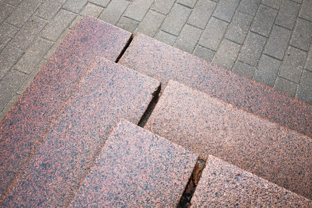 Stairs made of red granite on gray pavement photo