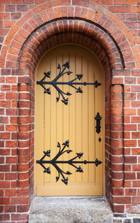 view of a wooden doorway: Gothic door in red brick wall of old Cathedral, Riga, Latvia