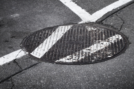 Round sewer manhole on asphalt road with white marking lines photo