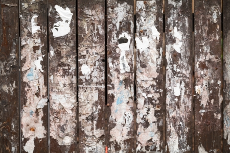 Old wooden fence background texture with scraps of paper ads photo