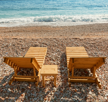 Wooden sun loungers stand on the Adriatic Sea coast photo