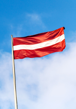 Flag of Latvia above blue sky with clouds photo