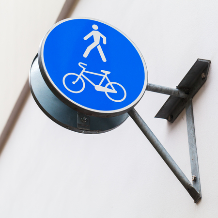 Blue pedestrian zone road sign on building wall photo