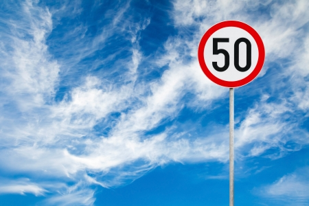 Round speed limit road sign above blue cloudy sky photo