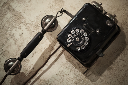 Vintage black phone hanging on old gray concrete wall photo