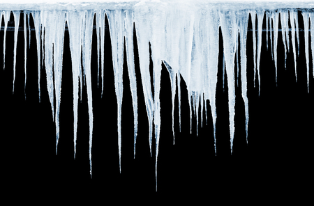 Group of icicles hanging on black background Stock Photo