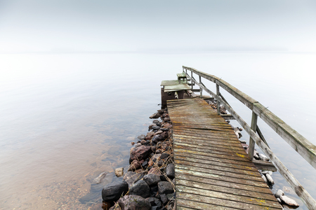 Old ruined wooden pier. Saimaa lake in foggy morning photo