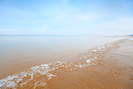 jurmala: Ice fragments on empty sandy coast of Baltic Sea