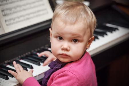 musica clasica: Pequeño bebé que juega la música en el piano clásico