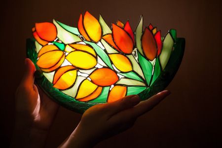stained: Handmade stained glass lamp with tulips flowers in womans hands Stock Photo