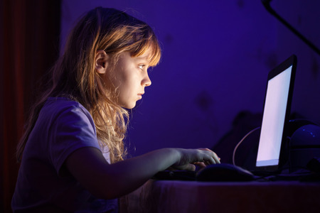 dark room: Little blond girl working on laptop in dark room at night Stock Photo
