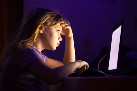 Little Caucasian girl working on laptop in dark room at night photo