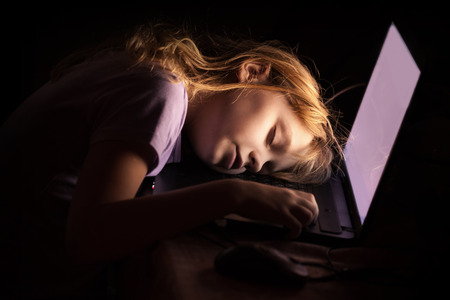 blond girl: Little blond girl sleeping on a laptop in dark room at night