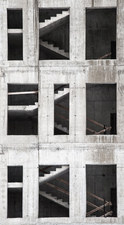 Building under construction, concrete wall with windows and stairs photo