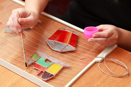 Stained glass maker works with colorful souvenirs photo