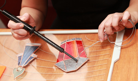 Stained glass maker works with red lamp souvenir photo