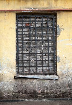 lattice window: Old yellow building facade with locked window