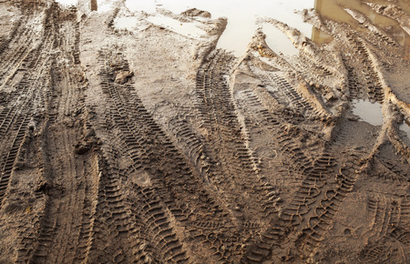 muddy tracks: Dark road dirt with tire tracks. Off-road transportation photo background