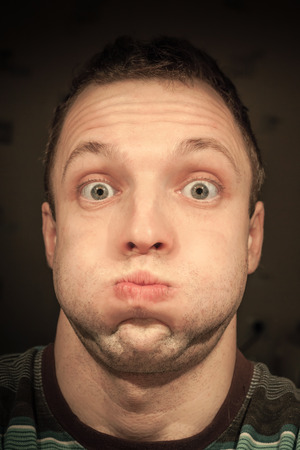 inflate: Young funny Caucasian man inflates cheeks. Closeup portrait