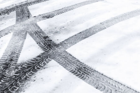 Automotive tire tracks on fresh wet snow photo