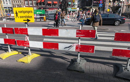 AMSTERDAM, NETHERLANDS – MARCH 19, 2014  Red and white striped warning road borders of street area under construction in historical center of the city