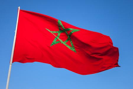 marocco: National flag of Morocco on a flagpole above clear blue sky