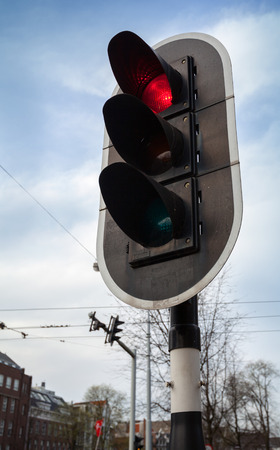 Red stop signal on black urban traffic light in Amsterdam photo