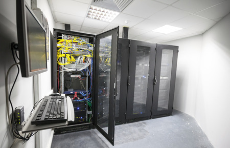 Modern server room interior with black computer cabinets and user terminal