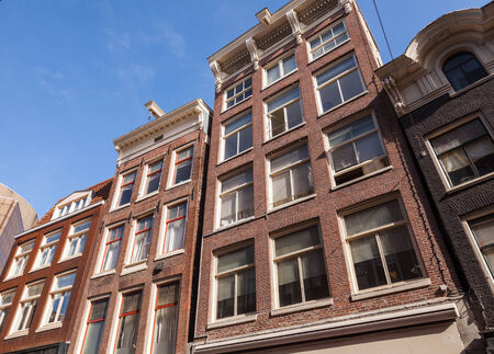 Red living houses facades with blue sky  Amsterdam, Netherlands photo
