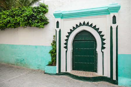 Green wooden gate of ancient mosque in Medina  Tangier, Morocco photo