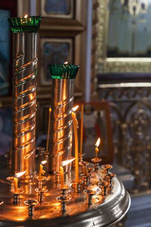 Candles are lit in a dark Orthodox Church photo