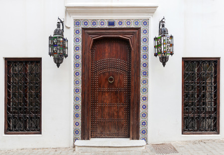 Ancient wooden door on white wall  Tangier, Morocco photo